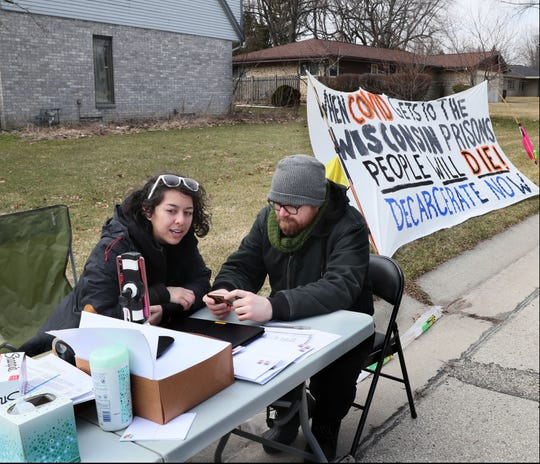 Tai Renfrow, left, and Ben Turk, citizen activists concerned about prisoners in the Wisconsin state system, do a livestream while they protest across the street from Department of Corrections Secretary Kevin Carr's house in Glendale. Their aim: To try and encourage him to reduce the prison population and address the COVID-19 threat. They set up a table to encourage people to write letters.