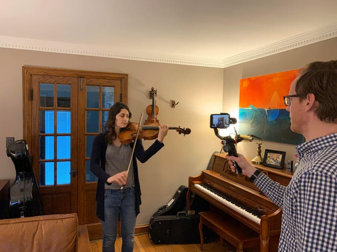 Lauren Roznowski Hayden plays a viola for one of her orchestra classes at Longfellow Middle School, while her husband, Mike Hayden, also an orchestra teacher within the Wauwatosa School District, helps film her.
