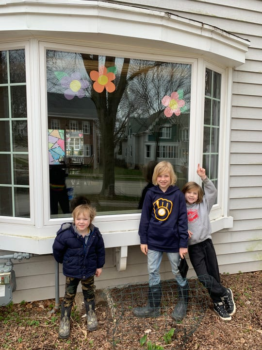 Kelly Goldmann's three children, Arlo (right), Jonah and Henry, show off some of their artwork in their window.