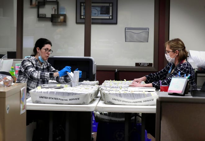Katherine Katsekes, left, and Diane Scott help sort absentee ballots by ward to be opened on election day at Brookfield City Hall on Tuesday. Many area communities are having a larger-than-normal number of residents voting early as concerns about the coronavirus raise questions about the upcoming  April 7 election.