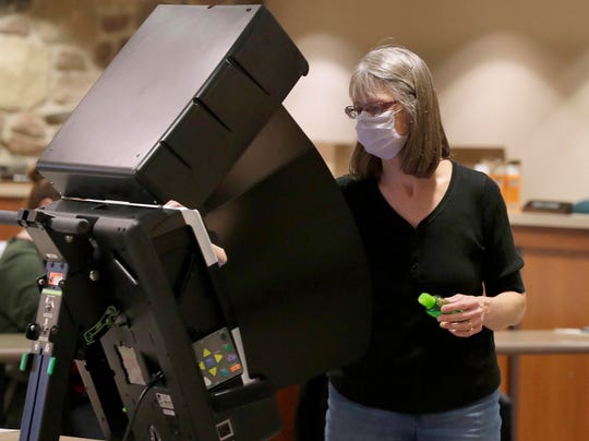 A helper wipes down each voting machine after a vote is cast at Brookfield City Hall on Tuesday, March 31, 2020. Many area communities are having a larger-than-normal number of residents voting early as concerns about the coronavirus raise questions about the upcoming election on April 7.
