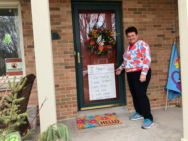 "Sue Lein, a retired kindergarten teacher who lives in Wauwatosa, shows an ""I spy"" sign she made in her front door. Families in the neighborhood have been stopping by her house to look for the items."