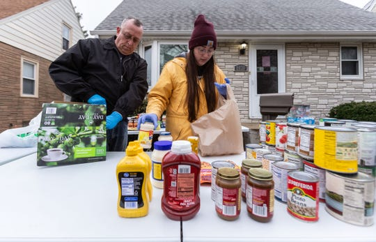 Don Gall of West Allis and his daughter, Dana, stock tables with donated food outside their home at 2630 S. 78th St. on March 31. The family set up a food pantry in their front yard to assist those in need during the pandemic.
