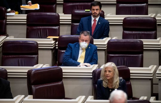 Rep. Proncey Robertson wears a mask as the house mets to postpone the session because of coronavirus in the House Chamber at the Alabama Statehouse in Montgomery, Ala., on Tuesday March 31, 2020.