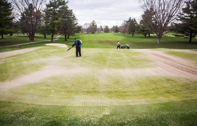 Staff at the Delaware Country Club golf course work Tuesday afternoon.