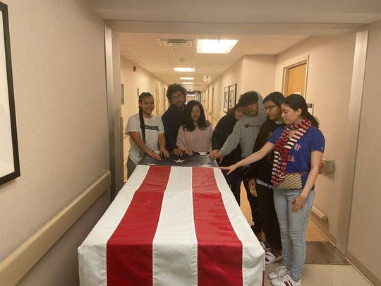 The Correa family grieves over the coffin of patriarch Col. Victor Correa, on March 18, 2020.