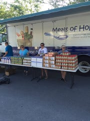 Volunteers prepare to distribute food items at a MOH mobile pantry site.