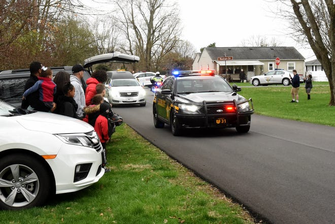 The Croom family, neighbors, and friends gathered to watch a procession of local law enforcement, including Licking County Sheriffs and Columbus Police, drive past the home of Annie Croom, widow of retired Licking County Sheriffs Office Sgt. George Croom, as part of the law enforcement officers funeral motorcade. George Croom is Licking County's first apparent coronavirus death.