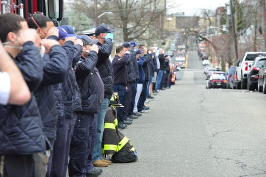 Passaic emergency personnel stand at attention for the release of the body of Passaic firefighter Tolentino Jr who died from complications due to the coronavirus at St. MaryÕs Hospital in Passaic, N.J. on Tuesday March 31, 2020.