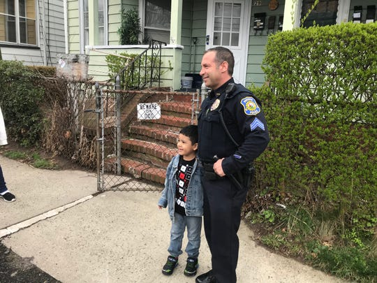 Sgt. Brian Dubac with Carlos Garcia, outside the 5-year-old's Linden Street home. Dubac and a dozen other police officers sang happy birthday to Carlos, who was sad his party had to be canceled.
