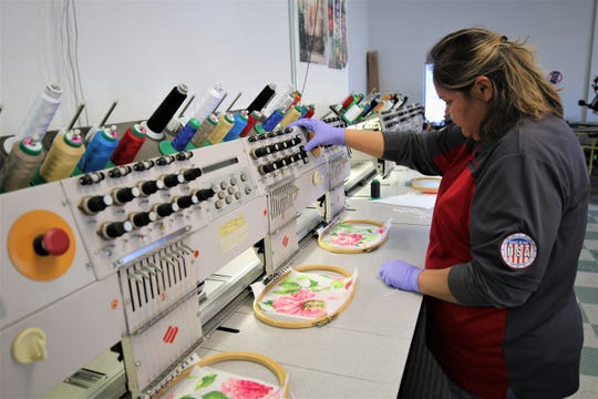Marcel Alen of Just Click Printing in Farmington operates a series of computerized embroidery machines to sew protective masks.