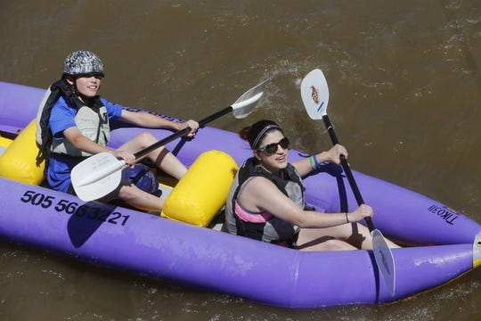 Kayakers paddle their way under the Berg Bridge on the Animas River during the 2017 Riverfest.