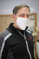 Jay Willmon of Just Click Printing in Farmington displays a prototype of the protective masks the company has been manufacturing.