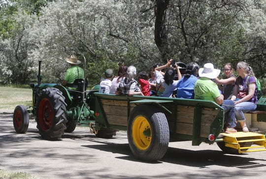 A group of Riverfest visitors enjoys a tractor ride during the 2017 event in Animas Park.