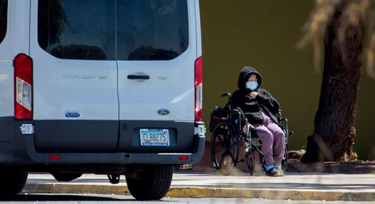 A patient sits outside while waiting for nurses at Sapphire of Tucson Nursing and Rehabilitation, 2900 E. Milber St., in Tucson, Ariz., on March 30, 2020.
