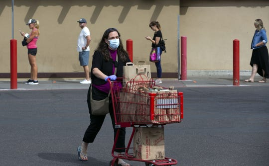A woman pushes her grocery cart back to her vehicle while shoppers keep social distance between each other because of the new coronavirus pandemic while lining up to enter the Trader Joe's at the Town and Country Shopping Center in Phoenix on March 31, 2020.
