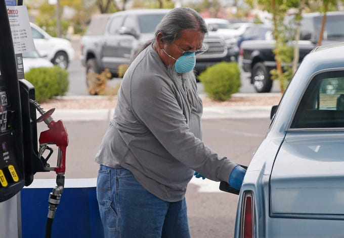 A man wears a mask and gloves to protect himself from the new coronavirus while pumping gas in Phoenix on March 31, 2020.