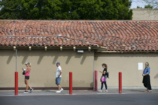 Shoppers keep social distance between each other because of the new coronavirus pandemic while lining up to enter the Trader Joe's at the Town and Country Shopping Center in Phoenix on March 31, 2020.