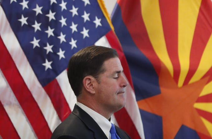 Gov. Doug Ducey listens to speakers on COVID-19 during a news conference at the Arizona Commerce Authority in Phoenix March 30, 2020. Gov. Ducey issued a stay at home order effective close of business March 31.
