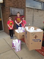 Lucas, Kylie, and Mason Saul of Lebanon Catholic School deliver paper goods to residents of Willow Terrance in downtown Lebanon. The students are collecting goods to help seniors through the pandemic.