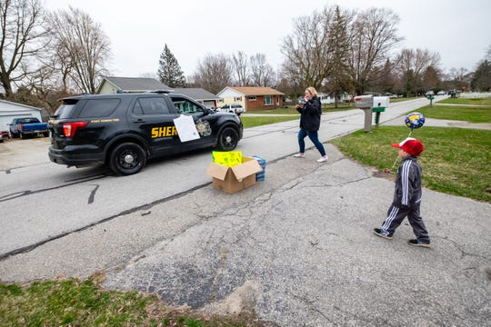 A St. Clair County Sheriff with a birthday card for Brednan Prevost, 5, right, drives past his house during a drive-by birthday celebration organized by The Dance Academy Tuesday, March 31, 2020, in Port Huron. Brendan couldn't have a birthday party because of the coronavirus pandemic, so friends and instructors from The Dance Academy, where he takes lessons, school drove by and wished him a happy birthday from a distance.