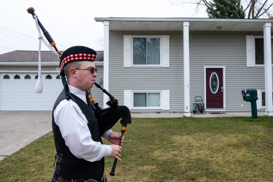 Wyatt Clarke, a freshman at Marysville High School, plays his bagpipes in front of a home in a Marysville neighborhood Tuesday, March 31, 2020. To help people stay happy during the coronavirus lockdown, he's been giving small performances around town.