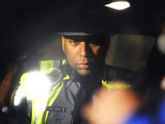 In this file photo from April 23, 2010, former state police Cpl. Carl Williams peers into a vehicle stopped at a DUI checkpoint on the business loop of Interstate 83 South.