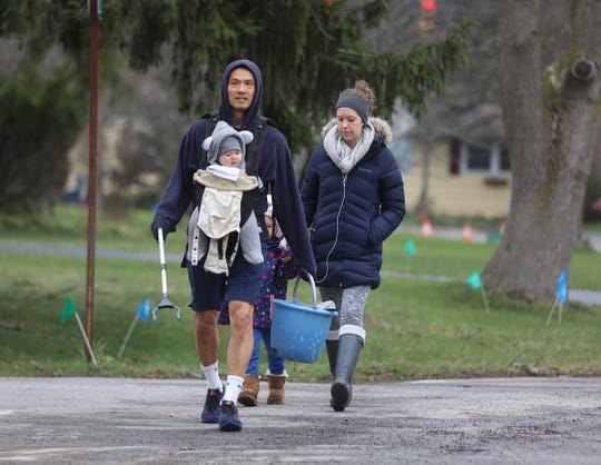 Hyeuo Park and his wife Clare, walk down Fairfield St. with their children Hae-jin, 4, and Joonie, six months, on March 31, 2020.  Park was picking up trash he found along the walk.