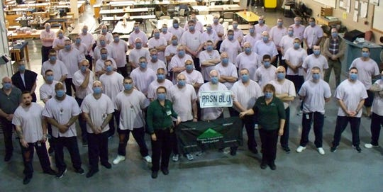 Oregon Corrections Enterprises wear masks they made at the factory where they normally produce blue jeans in Eastern Oregon.