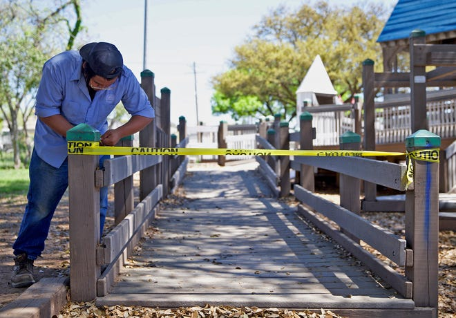 Abel Ibarra puts up tape to block off a playground on the Concho Riverwalk in San Angelo after city leaders made the decision to close off access to parks and other city recreational facilities in response to the coronavirus Tuesday, March 31, 2020.