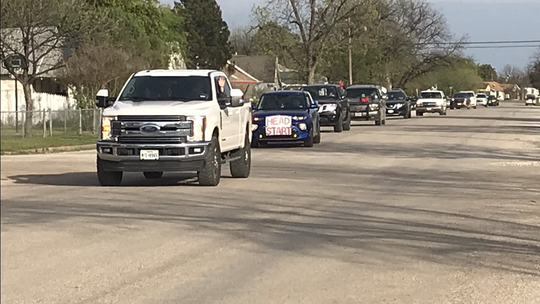 A line of vehicles drives down a street during a parade of Ballinger ISD employees Monday, March 30, 2020.