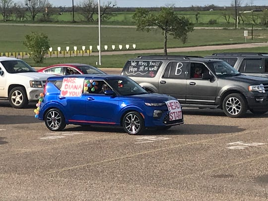 Ballinger ISD employees line up their vehicles in the parking lot of the high school before their parade through town Monday, March 30, 2020, due to students now missing a third straight week of scheduled classes because of the coronavirus pandemic.