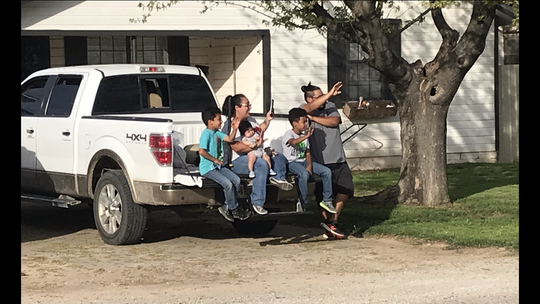 A family waves from the tailgate of their truck as a parade of teachers passes in front of their Ballinger home Monday, March 30, 2020.