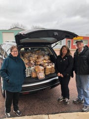 June Decker (left) and Kara Kubik join John Lambertus of Baltic American Legion Post 175 before the first Baltic Bread Bin on Sunday, March 29.