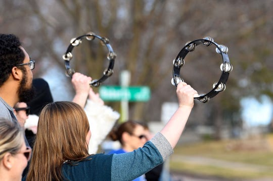 Teachers shake tambourines as students and their families drive by during a teacher/student appreciation parade on Monday, March 30, at Garfield Elementary School in Sioux Falls.