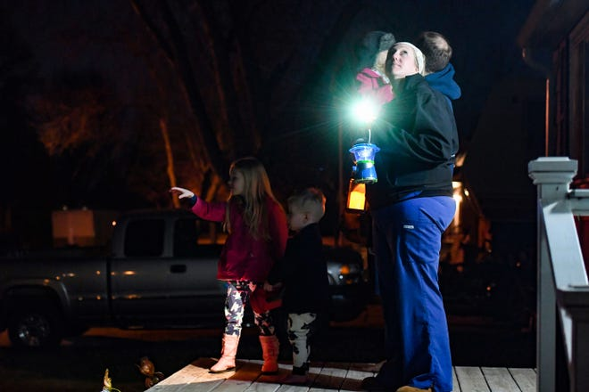 Heidi and Sam Drown help their kids, Eleanor, 5, Lucille, 4, and Silas, 2, look for the helicopter taking photos during Lighting Up Sioux Falls on Monday night, March 30. The event, from 9 p.m. to 9:15 p.m., was held to form solidarity during a time of social distancing during the pandemic.