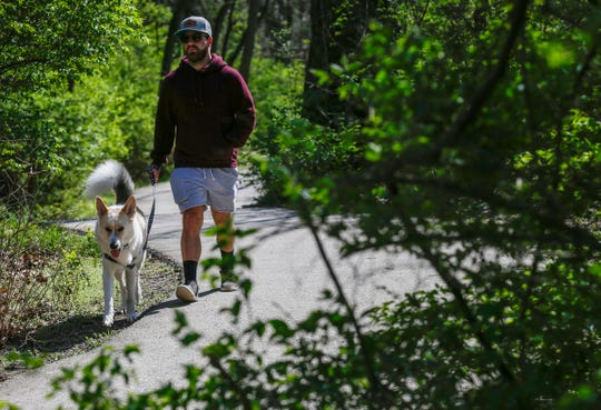 Tanner Crockett walks his dog Farley on the Ozark Greenways trail at Sequiota Park on Tuesday. Exercise and being out in nature are ways that people can help maintain their mental health during the novel coronavirus pandemic.