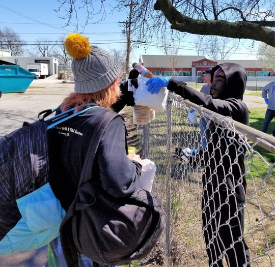 A Harbor House resident hands a to-go lunch over the fence to a homeless person.