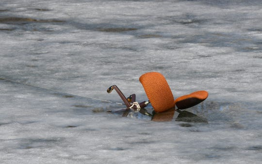 An orange office chair is partially submerged through the ice Monday, March 30, 2020, at Wolters Kluwer in St. Cloud. Each year an old office chair is placed on the ice in the fall and employees compete to guess the date and time it will fall through the ice in the spring.
