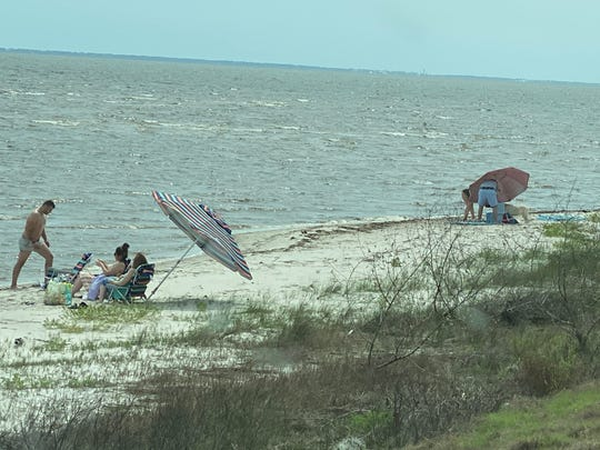 A small gathering of people on the beach between Eastpoint and Carabelle along U.S. Highway 98 who were issued notices to appear in court by the Franklin County Sheriff's Office for violating beach closure orders.