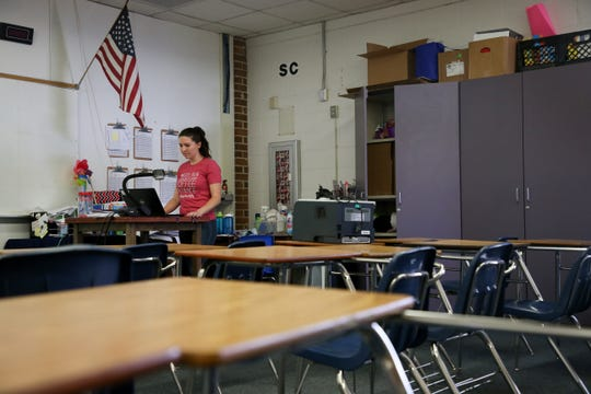 "Kaitlyn Harrison, a Fairview Middle School 6th grade teacher, works from her desk in her empty classroom, preparing for online instruction on ""the second first day of school"" Monday, March 30, 2020."