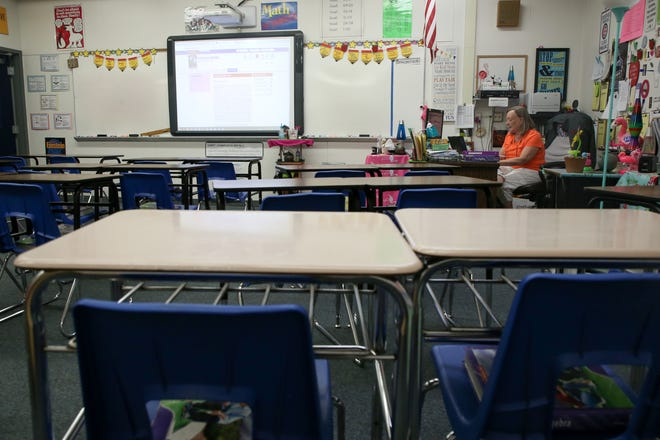 """Petra Burns, a Fairview Middle School 6th grade math teacher, prepares for online instruction from her desk in her empty classroom on """"the second first day of school"""" Monday, March 30, 2020."""