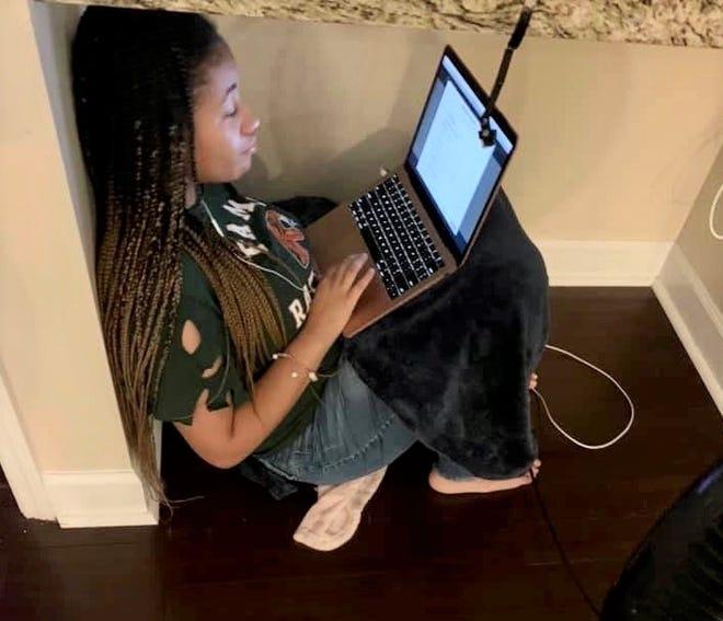 Amerie Ellis, 14, studies on her laptop during her homeschooling session.