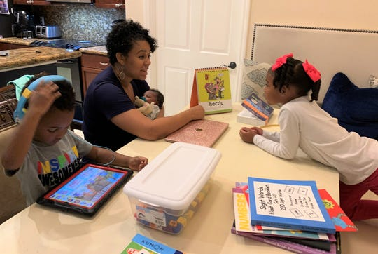 Shaia Simmons teachers her daughter Shailoh vocabulary words while Wraylon learns on his tablet during their homeschooling class.
