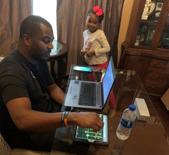 FAMU football head coach Willie Simmons draws up formations on his tablet while his daughter Shailoh watches during a break from their homeschooling work.