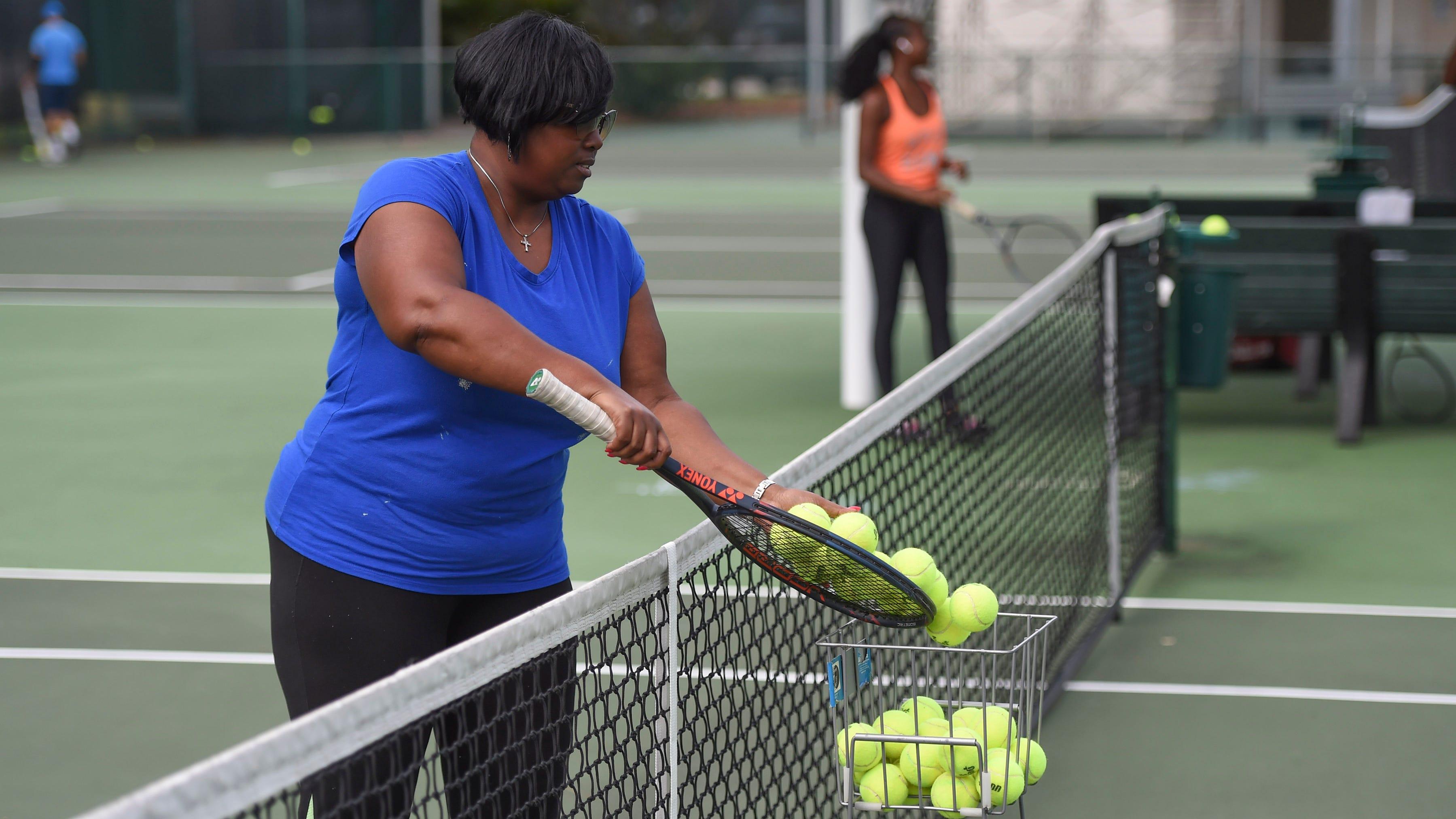 Les résidents jouent au tennis au Lawnwood Tennis Center le mardi 31 mars 2020, à Fort Pierce.  Les courts de tennis du complexe Lawnwood restent ouverts au public, avec des restrictions à l'entrée.
