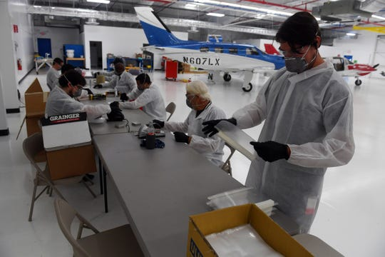 A small group of Piper Aircraft employees form a production line on Tuesday, March 31, 2020, making face shields for medical workers fighting the spread of COVID-19 at Cleveland Clinic Indian River Hospital. The production of the masks, which began last Friday, was for a total of 2,000 masks, but as the virus spreads, Cleveland Clinic has placed an order for 50,000.