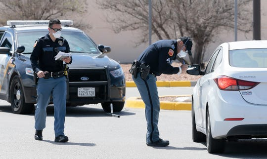Police officers wear protective gear as they screen patients entering the drive-through Coronavirus testing center Tuesday. Numbers of Coronavirus cases are on the rise in El Paso.