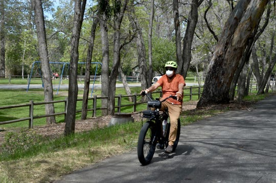 A bicyclist rides along the bike trail that runs along Foster Park on Tuesday, March 31, 2020. The County of Ventura prepared to close all of its parks as part of a statewide effort to slow the spread of COVID-19.