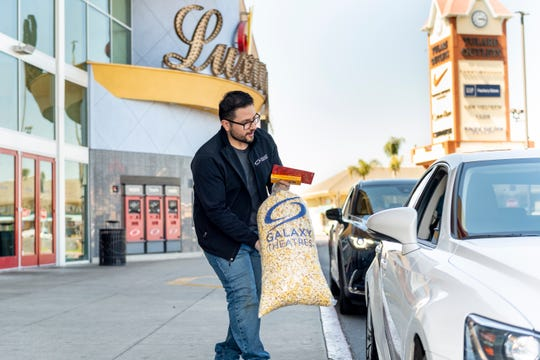 Freddie Gonzalez hands out free popcorn with $25 gift cards purchased at Galaxy Theatre in Tulare on Tuesday, March 31, 2020. All three poppers at the theater were in use to produce the 50 bags given out. Gonzalez is the General Manager. The offer will continue from noon to 2 p.m. Monday through Friday.
